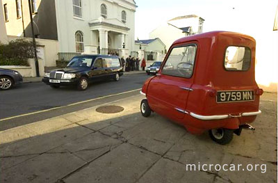 One of the few remaining Peel P50 microcars is passed by the coffin of its inventor and Peel Engineering Company founder Cyril Cannell
